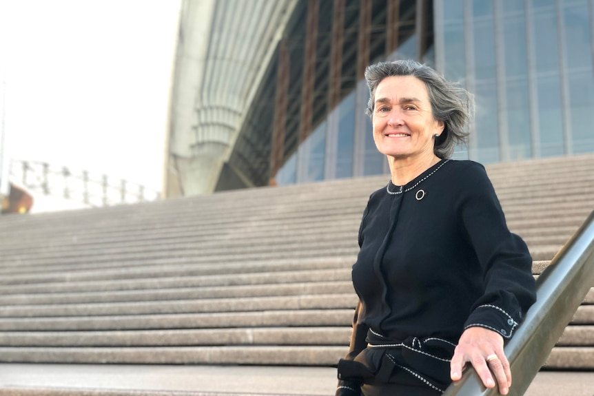 Louise Herron, wearing black, standing on the steps of the Sydney Opera House.