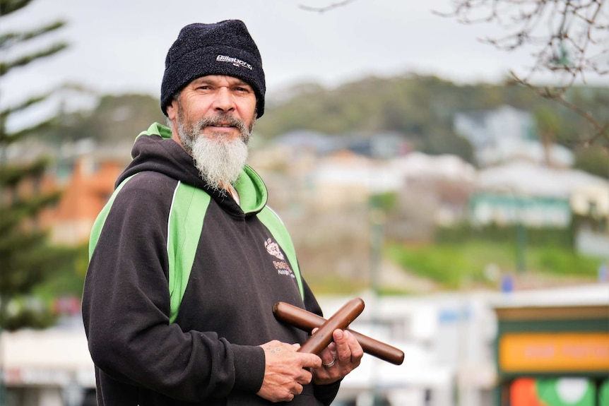 An Indigenous man standing outside wearing a beanie and hoodie, holding a pair of clapsticks.