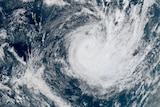 A satellite image of the South Pacific shows a portion of the Earth covered by a large cyclonic storm.