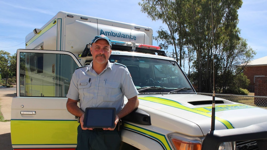 Officer in charge of Eidsvold ambulance station Scott Wicks stands in front of ambulance with his tablet.