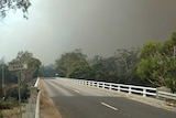 Smoke wafts over Coles Bay Road in Tasmania's north-east amid a fire emergency.