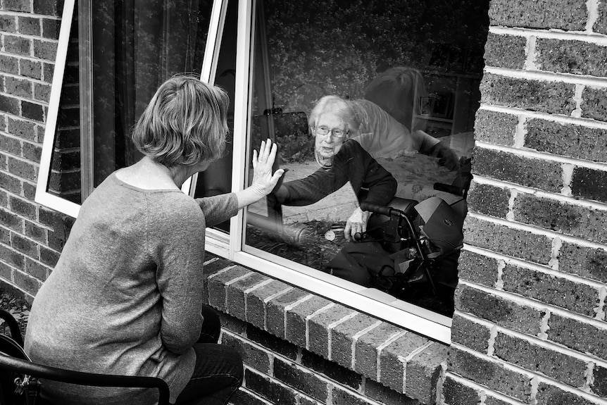 A black and white image of two women, one elderly, placing their palms together on the window that separates them.