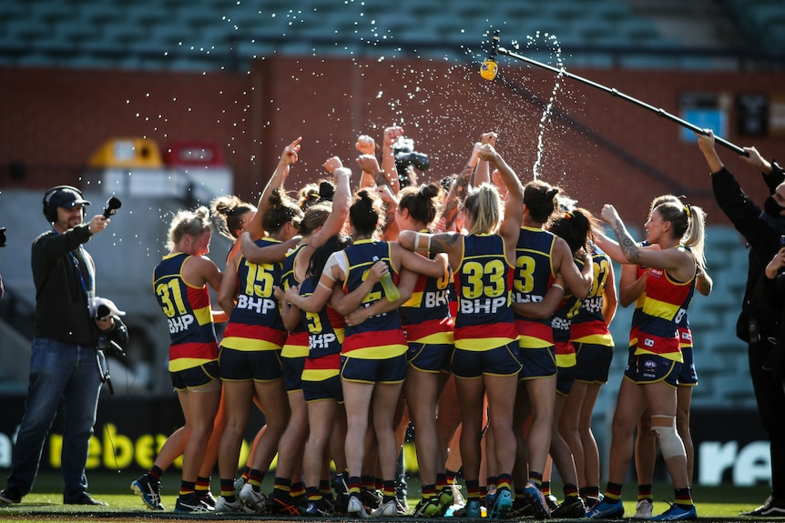 The whole Adelaide Crows team stand in a huddle and celebrate, squirting water everywhere