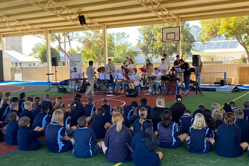 School students in blue uniform watch a band perform.