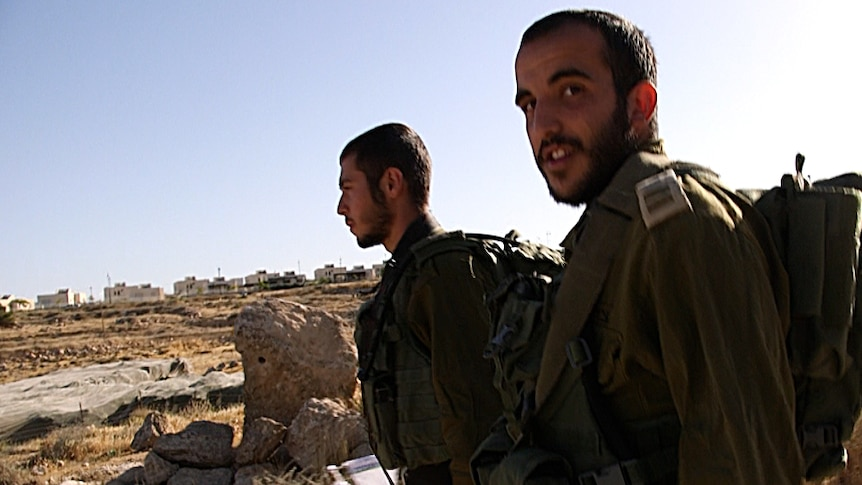 Two Israeli Defence Force troops walk, accompanying teenagers on their way to school, past an Israeli settlement.