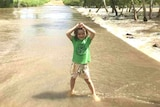 A young girl wearing a green shirt playing in shallow flood water.