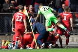Adelaide United players jump into a pile of bodies in front of spectators in a grandstand