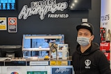Naty heng wears a mask while standing in his empty burger shop in Fairfield.