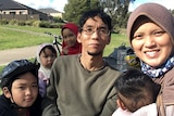 Woman in hijab smiles on right of frame, man and four children by side.