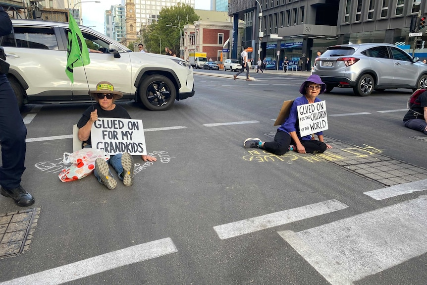 Two protesters sitting on Flinders Street