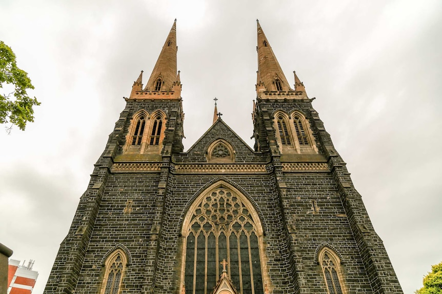 The facade of St Patrick's Cathedral reaches into a cloudy sky.
