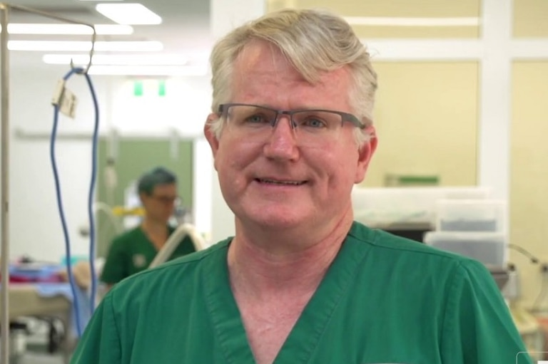 A man wearing clear glasses wearing green hospital scrubs standing in an animal hospital theatre