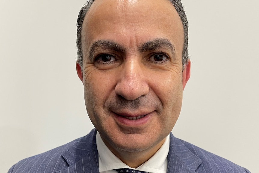 Dr Walid Ahmar looks at the camera while wearing a suit and tie in a passport-style photo.