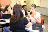 Vanessa at a desk at Edith Cowan University with peers Olivia Muhanga (left) and Kayla Edwards, and interpreter Alana Wiekart.