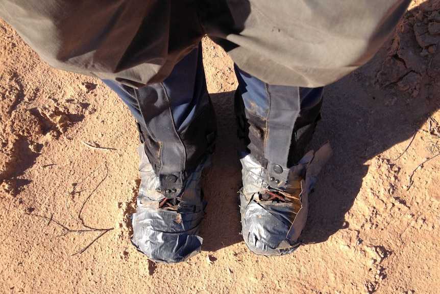 A man's boots wrapped in gaffer tape.