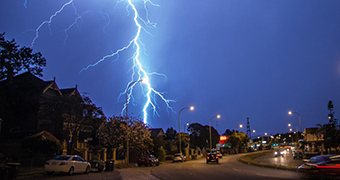 A bolt of lighting strikes from cloudy skies over a suburban street.
