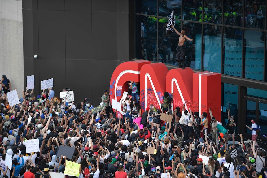 The red CNN logo is seen outside the broadcaster's building, with some people on it and hundreds standing in front of it.