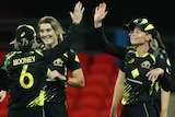 Four Australian players celebrate during the win over India in the third women's T20 international.