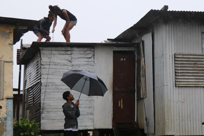 Two girls stand on the tin roof of a building in the rain, while a man below holds an umbrella.