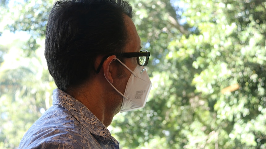 A man in a face mask stares out a window