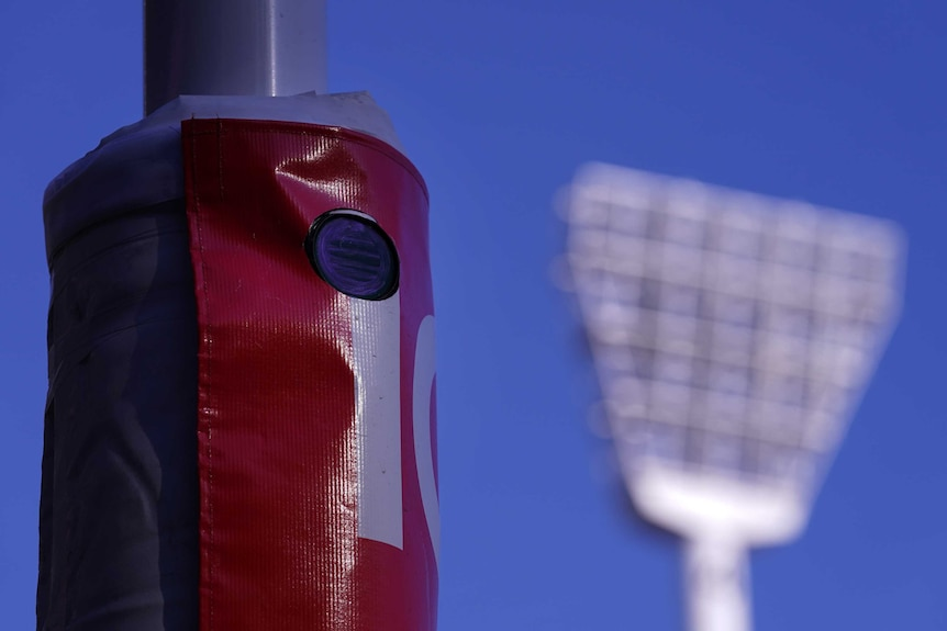 A small, round camera can be seen inside the padding around a goalpost. A floodlight is in the background