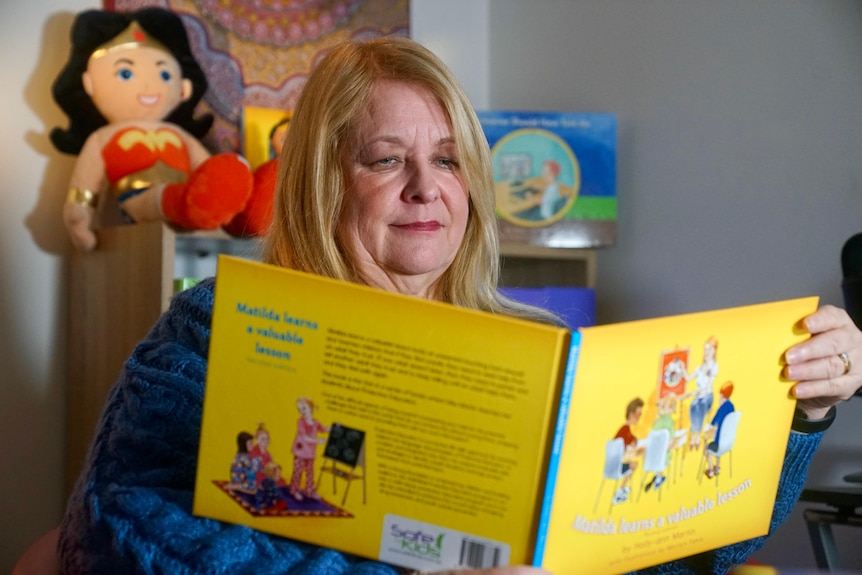 A woman sits in front of a bookshelf reading a childrens book