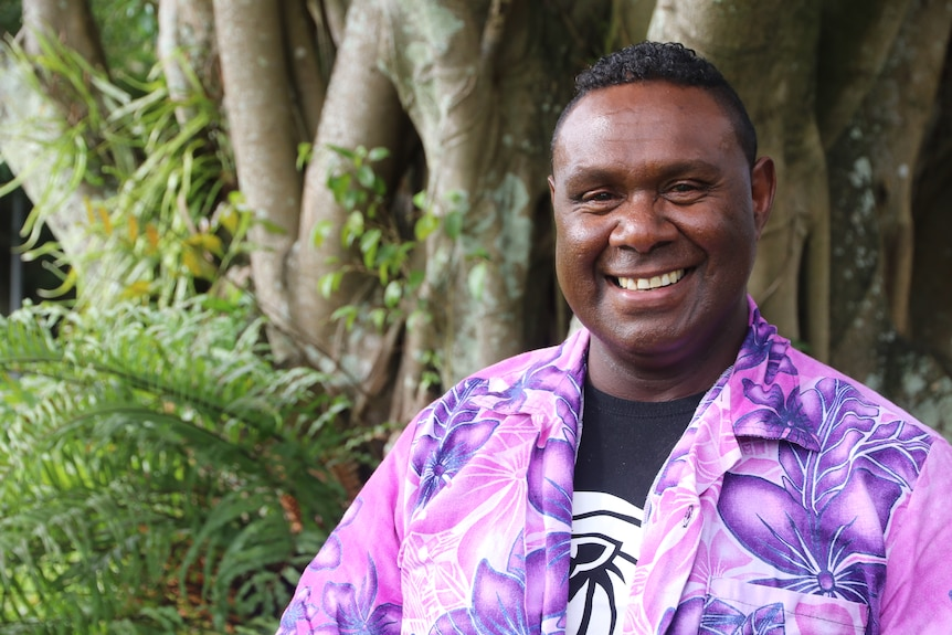 Pastor Ned Gebadi is wearing ao bright purple and pink shirt that's tropical patterned with a black and white T shirt underneath