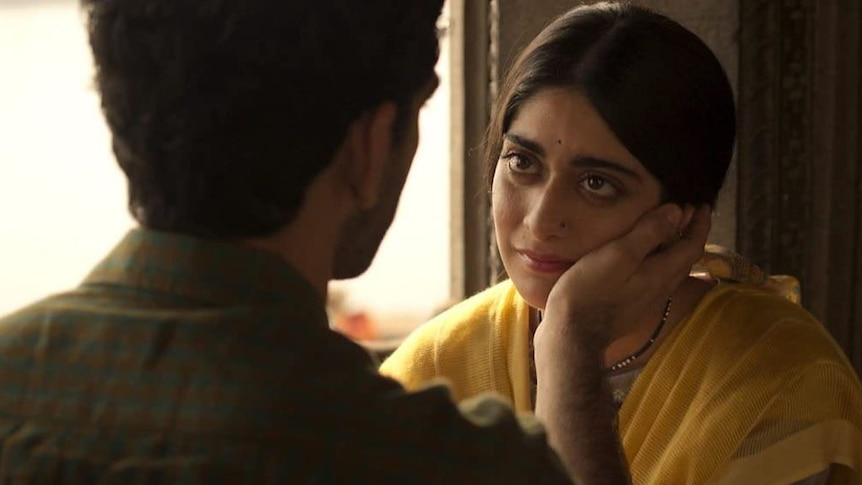 A woman with dark hair wearing a yellow sari stares at a man in profile against a window.
