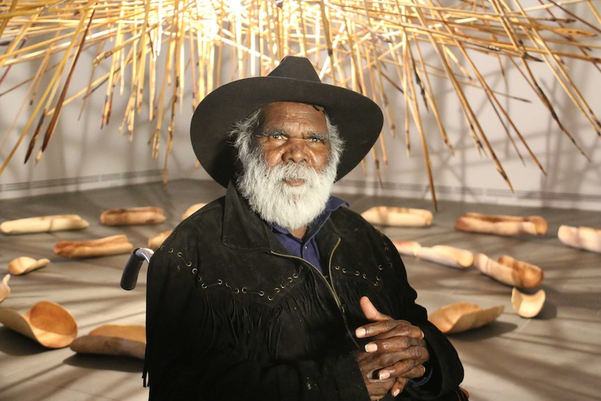 Aboriginal artist Mike Williams sits in front of an installation.