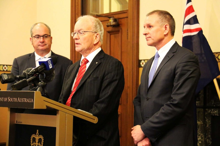 Three men in suits stand behind a podium with Australian flags in the background.