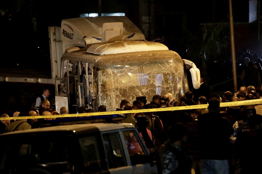 A crowd of officials gather near the front of a mini bus with a shattered windscreen and blown out sides.