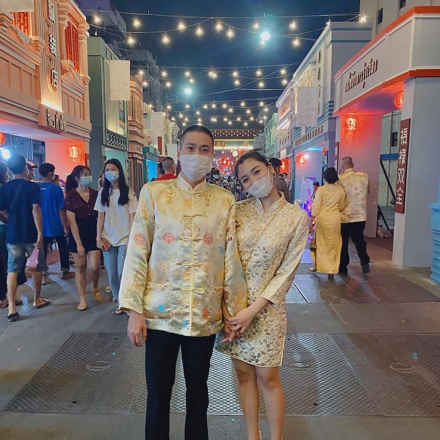 A man and a woman in face masks stand holding hands in a street with fairy lights strung up behind them