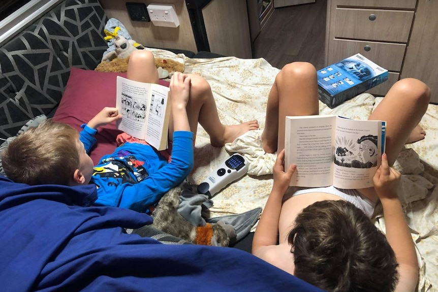 Young kids reading on a bed.