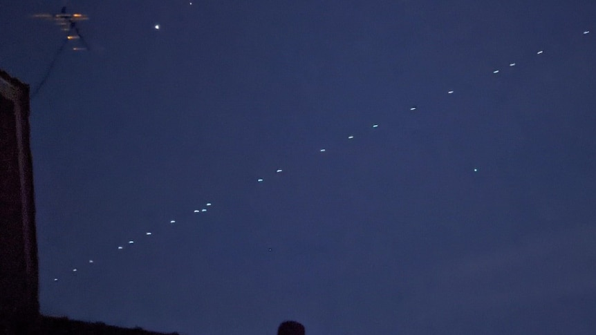 A photo of dozens of lights in a row across the night sky.