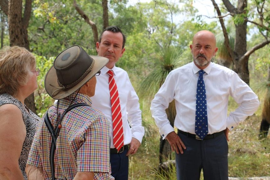 Labor candidate Hugh Jones and WA Premier Mark McGowan stand talking to a man and a woman in bushland.