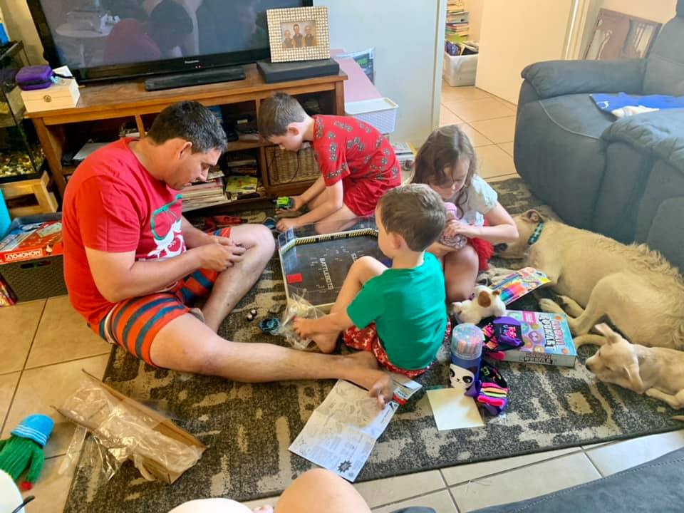 A dad plays with his three children on the floor of a living room