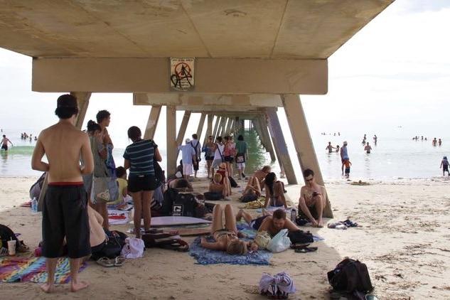 Beach-goers huddle under a jetty