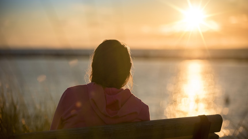A woman sits on a park bench, her back to the camera, as the sun sets over water