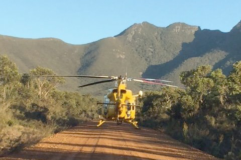 A rescue helicopter on a dirt track in the Stirling Range National Park with mountains in the background.
