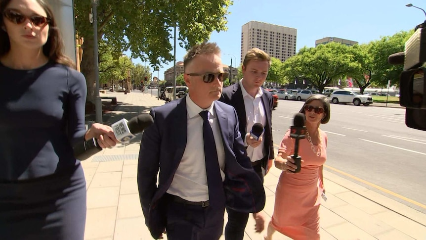 A man in a blue suit and glasses surrounded by reporters walking quickly