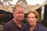 A man and a women put their arms around each other with a destroyed house behind them