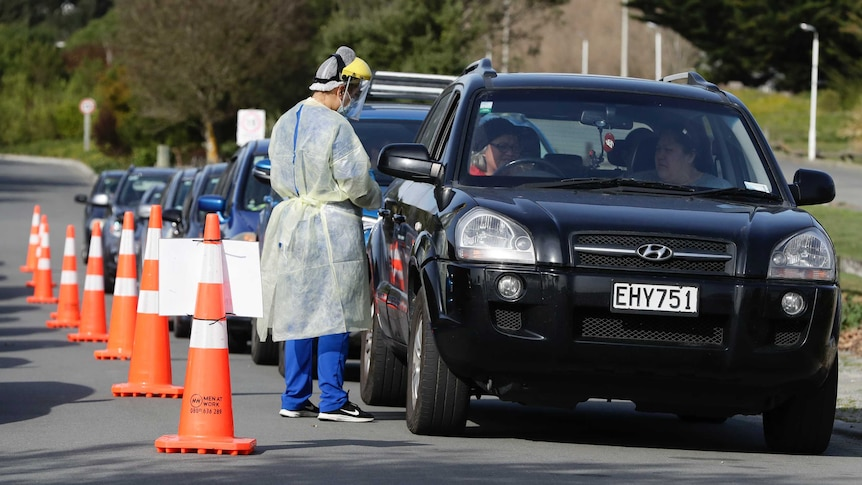 Medical staff prepare take a COVID-19 test from a visitor to a drive through testing point in Christchurch, New Zealand.