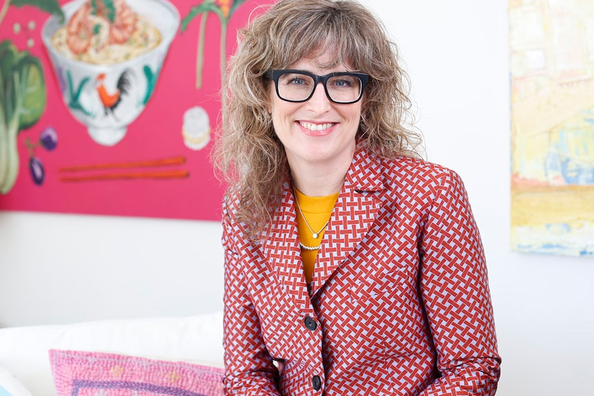 Laura Higgins wears a red, checkered jacket and sits in front of some bright modern paintings.