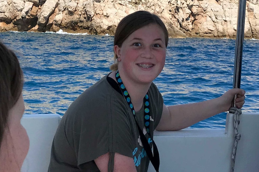 Kate smiles at the camera. She is on a boat, in front of what appears to be a castle or fort.