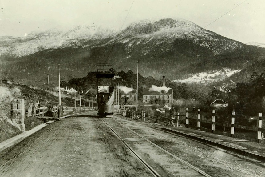 Old black and white photograph of a tram on a wide road and a snow covered mountain behind it