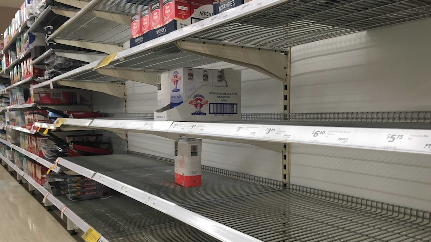 rows of supermarket shelves have been emptied of flour