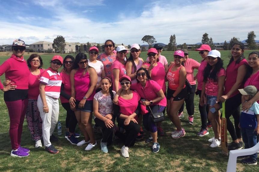 A dozen women in pink shirts pose around a cricket pitch.