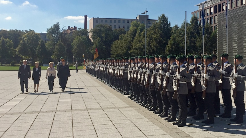Australia and Germany's foreign and defence ministers walk past a row of troops in Berlin during high-level security meetings.