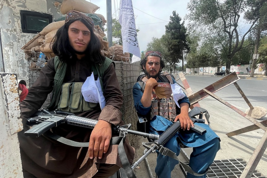Two members of Taliban forces sit at a checkpost in Kabul with guns on their lap.