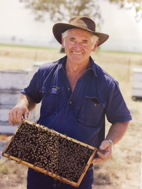 Rex Carruthers holds a hive frame.